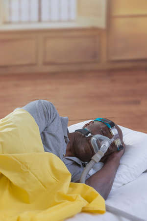 Healthcare concept,African, American Man with obstructive sleep apnea sleeping well with cpap machine ,Man laying in bed wearing cpap mask, in a luxery house or hotel bacground
