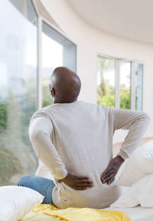 African American man with severe backache sitting on bed in his luxery bedrooms appartment Stock Photo
