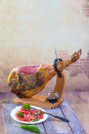 Jamon. Jamon serrano. Traditional Spanish Dry cured spanish pork ham in a plate with knife on old vintage wooden background Archivio Fotografico