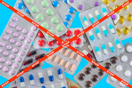 blisters of medical pills over blue background with stop crossed ribbon as a pharmaceutical industry concept danger