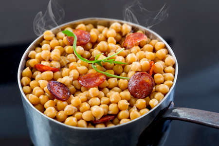 real homemade chickpeas, steaming stew with chorizo on a black background Archivio Fotografico