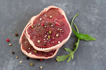 Tournedos: a small round thick cut from a fillet of beef grey slate background above view