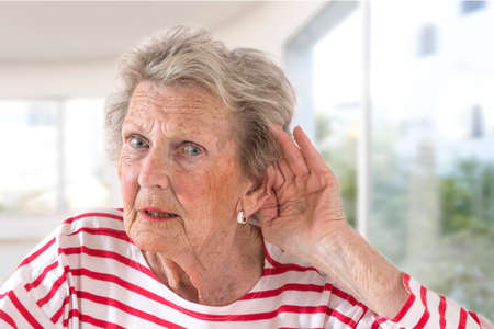 Elderly lady with hearing problems due to ageing holding her hand to her ear as she struggles to hear, profile view on large windows background Foto de archivo