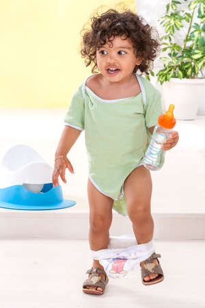 Young boy standing in green knitted jumpsuit , diapper on legs, holding water from a bottle iwitn a white and blue potty on background Stock Photo