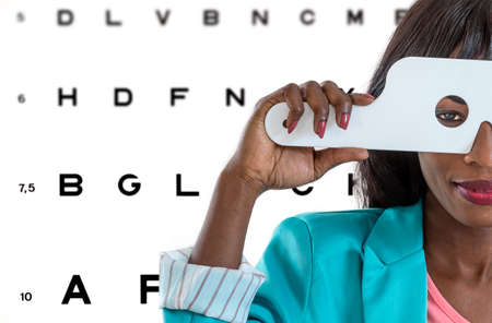Young African lady taking an eyesight test examination at an optician clinic whith Eye Chart Illustrations on background