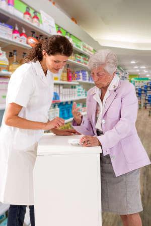 medicina, farmacia, atención médica y concepto de personas - farmacéutico feliz mostrando instrucciones de drogas a una cliente mayor en una farmacia