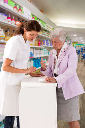 medicine, pharmaceutics, health care and people concept - happy pharmacist showing drug lnstruction to senior woman customer at drugstore