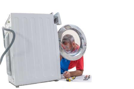 plumbing. Plumber repairing washing machine on white background