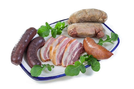 Selection of French Raw sausage with arugula leaves in a plate isolated on white background.