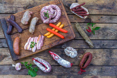 Selection of French Raw charcuterie board, with arugula leaves and dry sausage over a wooden background