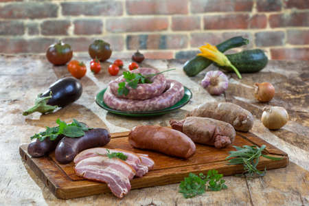 Selection of French Raw sausage with arugula leaves in a wooden board,vegetable on the table on old red brick background.