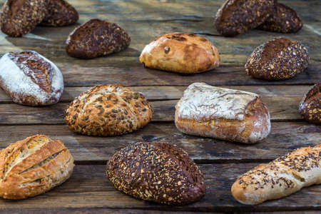 Several small multi grain different shaped bread sprinkled with whole sunflower seeds, flax and sesame seeds and wheat and barley spikes on old brown wooden table