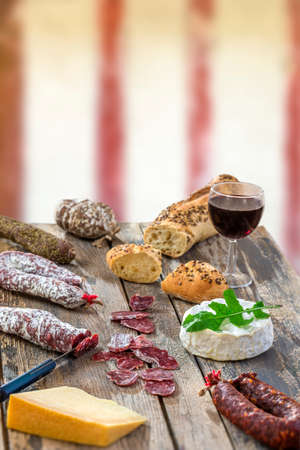 French Snacks with wine - various types of cheeses, bread , dry suassages, charcuterie, red vine on a gray background. . Food background over timbered wall