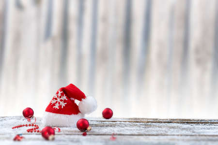 Christmas background with christmas ball, gift, red hat and snow on a wood board,over white old wooden wall Stock Photo