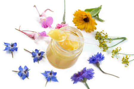 raw organic royal jelly in a small bottle with litte spoon on small bottle surrounded by flowers on old white background 版權商用圖片