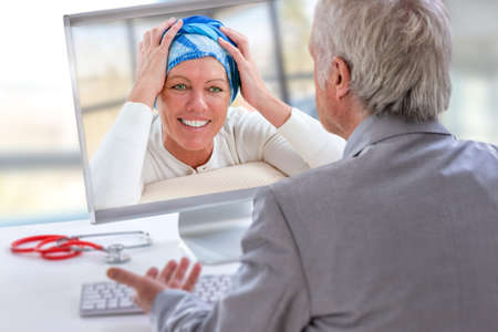 Telemedicine or telehealth concept, Doctor on the computer laptop screen and patient with cancer wearing headscarf, conferencing on treatment Stock Photo