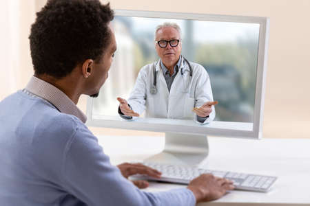 In-home care for a young male patient with telemedicine or telehealth, virtual live chat. Stockfoto