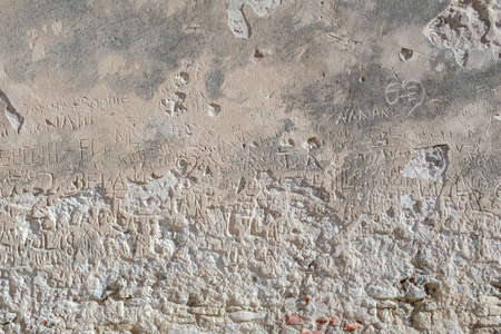 Engraved writings on stone wall by tourists to show their passage-message, name....