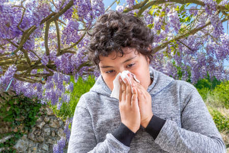 Pollen Allergy. Danger, Tennage boy sneezing in a flowers meadow. Concept: seasonal allergy.