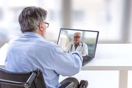 Consultazione remota per paziente disabile- Medico che conforta un paziente disabile Archivio Fotografico
