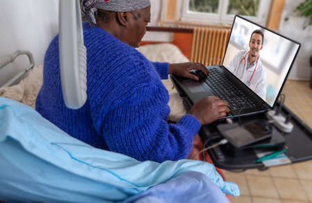 Businesswoman continue homeworking At the time of home hospitalization. Stay in bed. having internet consultation with her doctotor Stock Photo