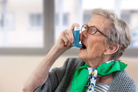Close-up of senior woman using asthma inhaler.