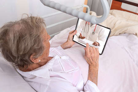 Sick senior woman with tablet pc Stay in bed at home having internet consultation with her doctor