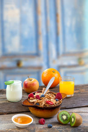 Healthy breakfast with natural yogurt, muesli and berries on white wooden background, closeup, horizontal Banco de Imagens - 124986478
