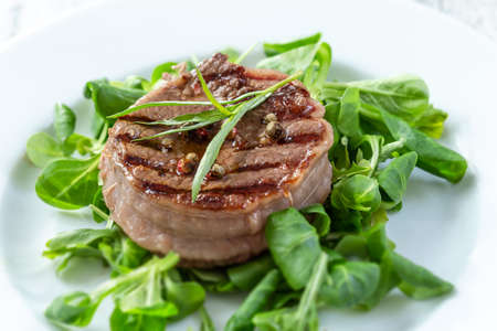 Rump Steak with Green vegetable, spinach,, pepper close up on plate