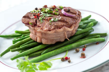 Rump Steak with Green vegetable,French beans, pepper close up on plate