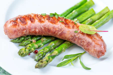Grilled sausages with asparagus on plate with tarragon, coriander code up