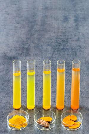Healthcare Resaerch on Curcuma. test tube with mater and curcuma with turmeric powder and turmeric root on slate background Фото со стока
