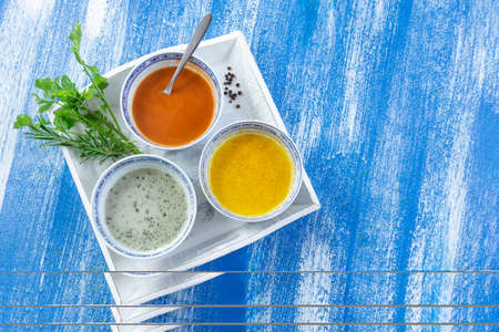 Colorful green, yellow and red spicy sauces in bowls in a white plate isolated on blue wooden painted plank