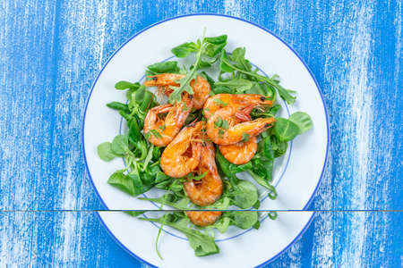 Healthy salad plate. Fresh seafood recipe. Grilled shrimps and fresh vegetable salad . Healthy food. Flat lay. Top view on blue wooden background Stockfoto