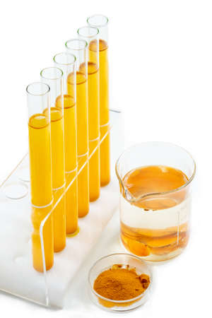 Healthcare Resaerch on Curcuma. test tube with mater and curcuma with turmeric powder and turmeric root on White background