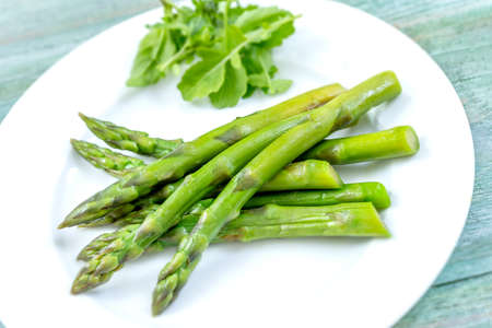 Cooked asparagus on the plate. Season, green background