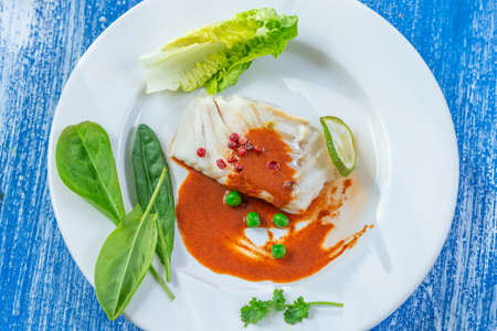 Plate of Steamed fish with paprika sauce with salad