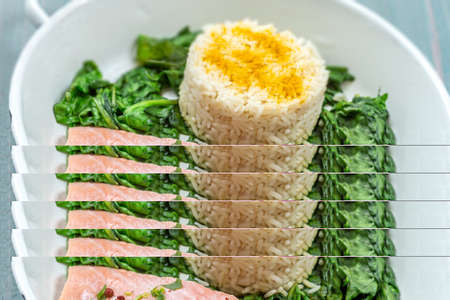 Salmon fillet with rice and spinach garnish. Fish steak. Lemon salmon on white plate on wooden background