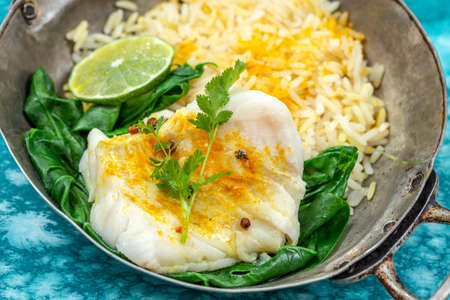 Cod fillet with rice and spinach garnish with curry, in vintage pan on blue marbled wooden background Banco de Imagens