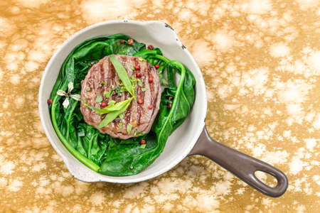 Sirloin steak rare with and spinach steam cooked served in a vintage pan on marbled yellow wooden table. Rustic style.
