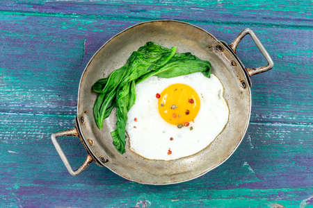 Rustic Pan with fried egg and steam cooked spinach on a green-purple painted table