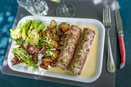 Andouillette, lyonnaise sausage, french food on blue background