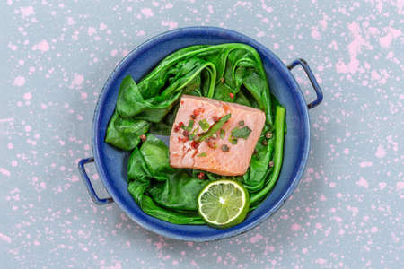 Salmon fillet with rice and spinach garnish. Fish steak. Lemon salmon on vintage pan on wooden background Banco de Imagens