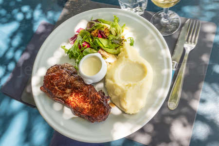 white plate of a pork chop with mashed potatoes meal, luxury atmosphere diner