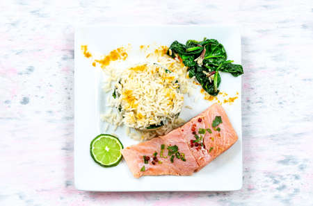 Salmon fillet with rice and spinach garnish. Fish steak. white plate on grey paint brush wooden background