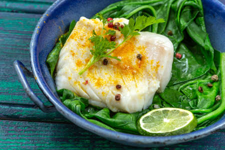 Cod fillet with rice and spinach garnish with curry, in vintage pan on wooden background