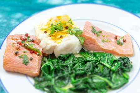 Cod and Salmon fillet with rice and spinach garnish. Fish steak. Lemon salmon on white plate on wooden background