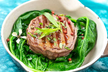 Sirloin steak rare with and spinach steam cooked served in a vintage pan on blue wooden table. Rustic style.