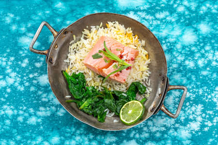 Salmon fillet with rice and spinach garnish. Fish steak. Lemon salmon on old pan on blue marbled paint wooden background Banco de Imagens