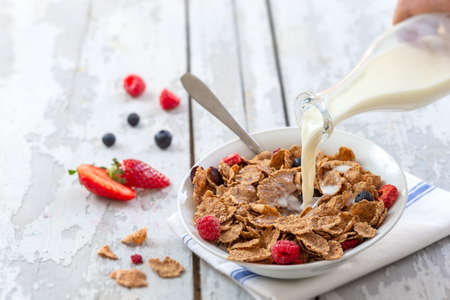 Healthy cereal breakfast. with Berries - fresh strawberries and blueberries, with milk pourring on old wooden table